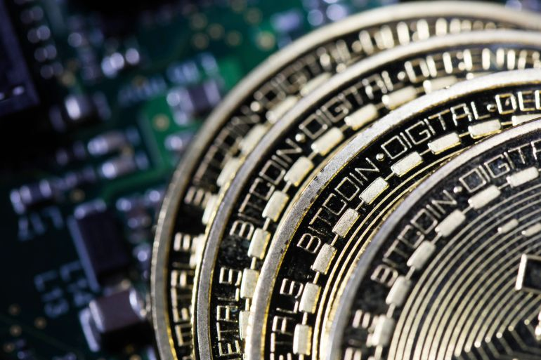 Three coins representing Bitcoin cryptocurrency sit on a computer circuit board in this arranged photograph in London on February 6, 2018 [Chris Ratcliffe/Bloomberg]