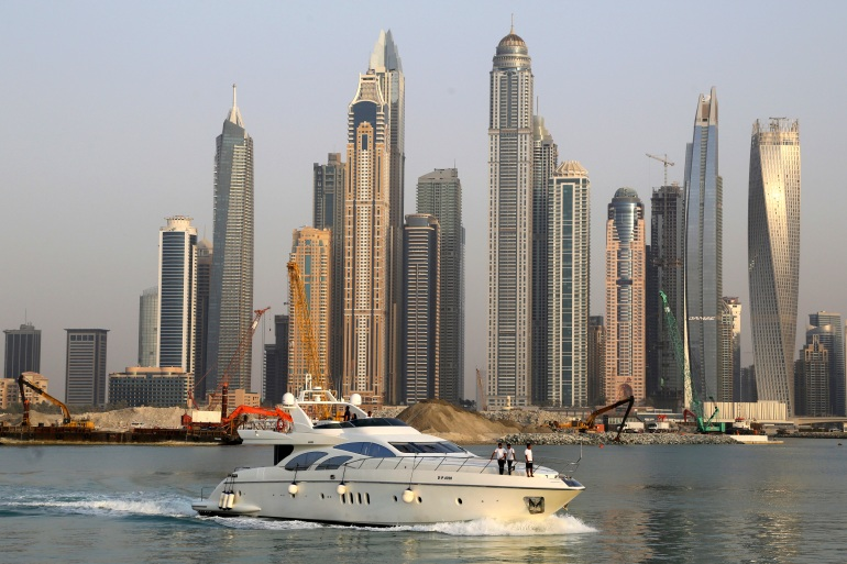 A boat speeds past giant skyscrapers at the Marina waterfront seen from Palm Jumeirah island in Dubai [File: Aijaz Rahi/AP Photo]