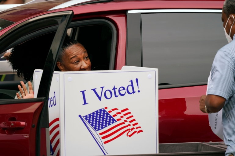 A voter finishes selecting her choices from a vehicle during early voting in Dallas, Texas, the United States [M Otero/AP Photo]