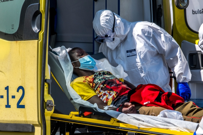 A refugee is taken on a stretcher by medical workers as he arrives at the Arguineguin port in Gran Canaria island, Spain, after being rescued in the Atlantic Ocean by emergency workers on October 20 [Javier Bauluz/AP Photo]