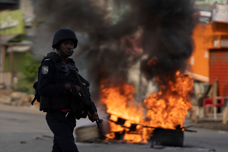 A policeman walks past a burning barricade during a protest after security forces blocked access to the house of the former president Henri Konan Bedie [File: Leo Correa/AP]