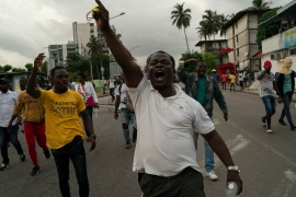 An opposition supporter protests after security forces blocked access to the house of the former president, Henri Konan Bedie, in Abidjan, Ivory Coast [Leo Correa/AP]