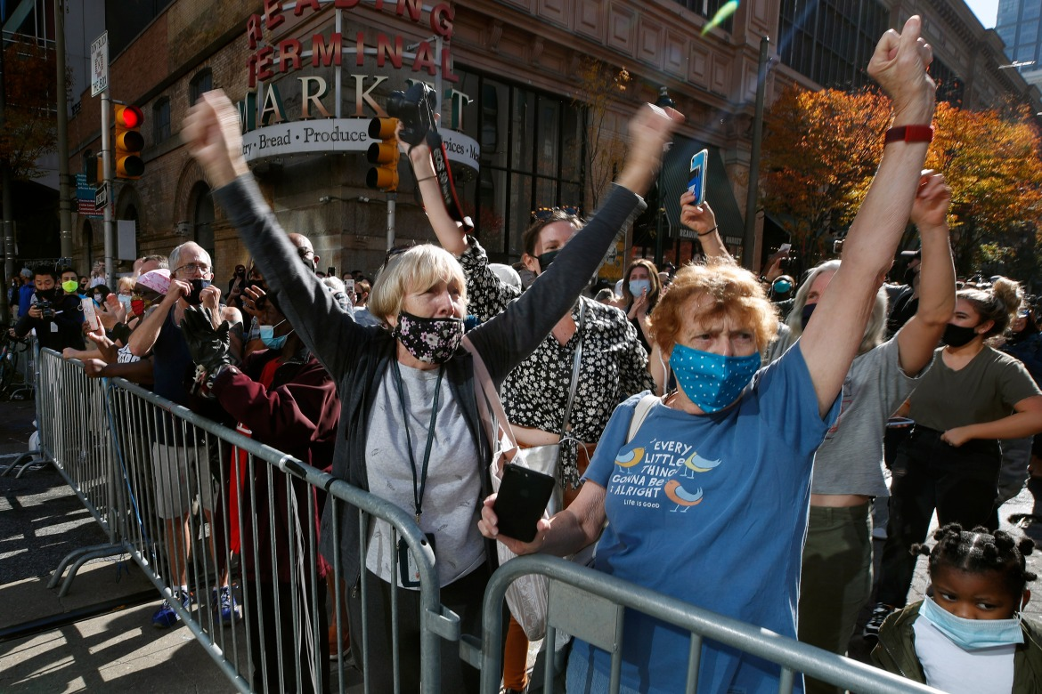 People celebrate outside the Pennsylvania Convention Center in Philadelphia, after Democrat Joe Biden defeated President Donald Trump to become 46th president of the United States. [Rebecca Blackwell/AP Photo]