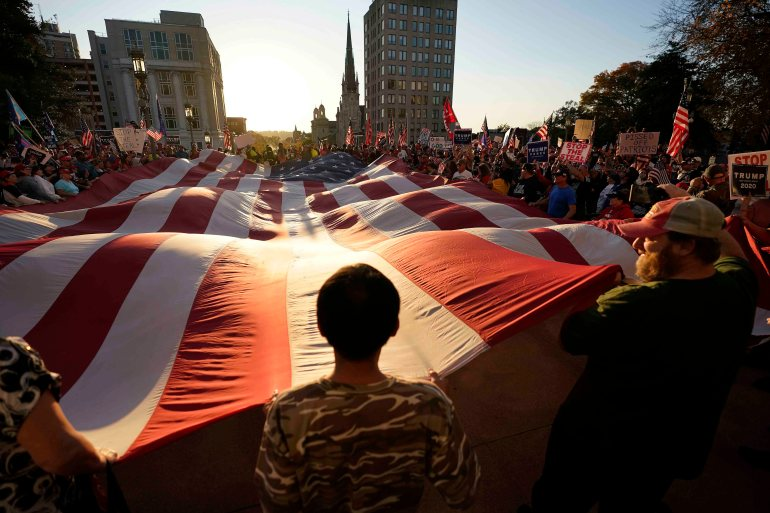 Supporters of President Donald Trump unfurl a giant American flag outside the Pennsylvania State Capitol in Harrisburg, US on November 7, 2020 [AP/Julio Cortez]