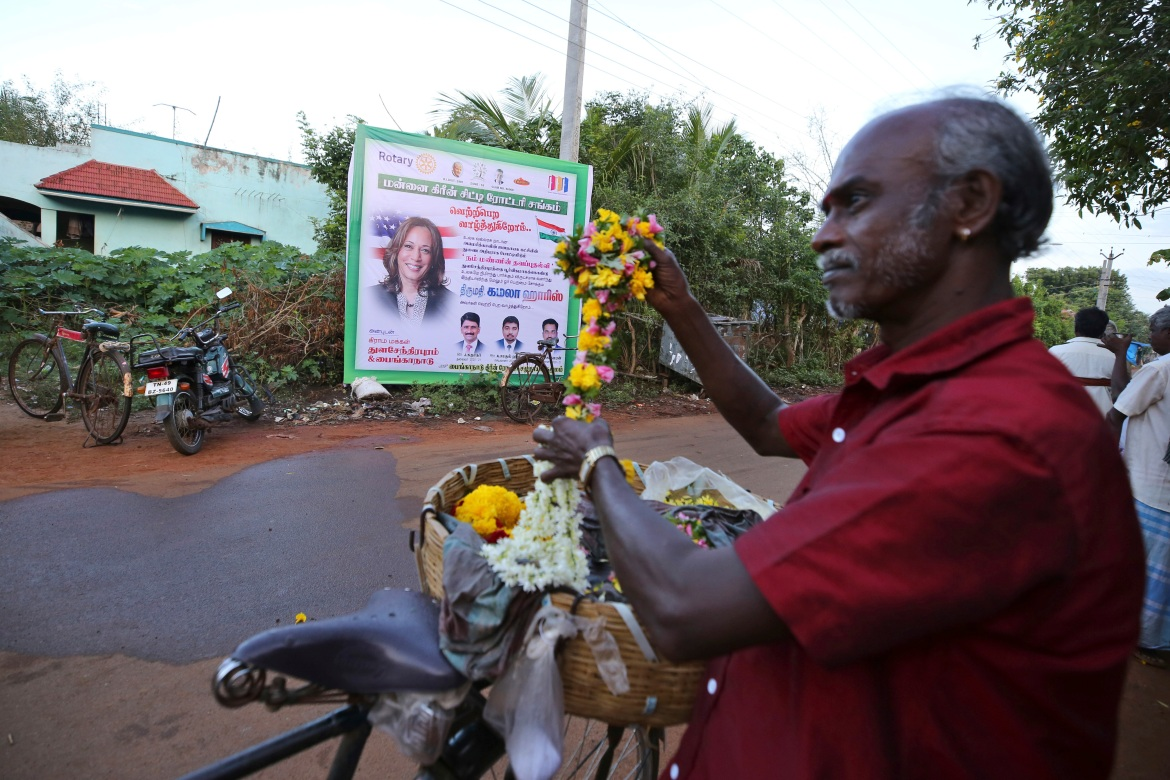 A vendor sells flowers in front of a hoarding featuring US Vice President-elect Kamala Harris in the hometown of Harris's maternal grandfather, in Thulasendrapuram, south of Chennai, Tamil Nadu state, India. [Aijaz Rahi/AP Photo]