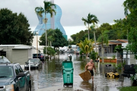 Residents clearing debris from a flooded street in the aftermath of Tropical Storm Eta in Davie, Florida. [AP Photo/Lynne Sladky]