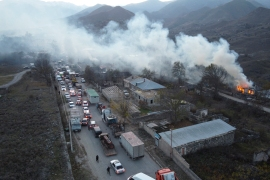 Smoke rises from a burning house as cars and trucks are stuck in along the road from Kalbajar leaving Nagorno-Karabakh to Armenia on November 14, 2020 [Dmitry Lovetsky/AP Photo]