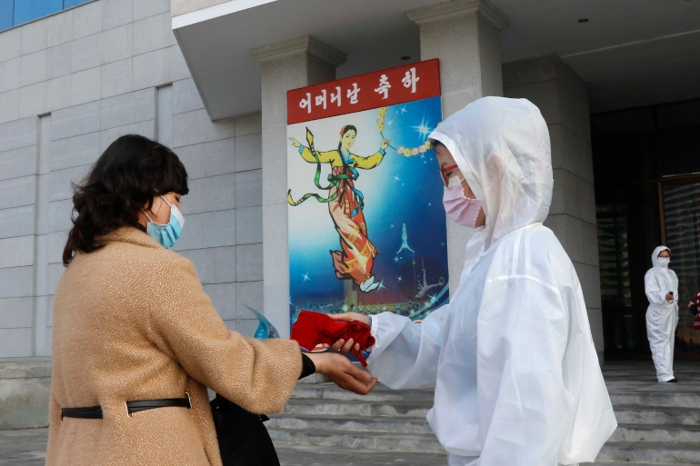 A woman has her temperature checked outside a perfromance for Mother's Day in Pyongyang, North Korea, Monday, November 16, 2020 [Jon Chol Jin/ AP]