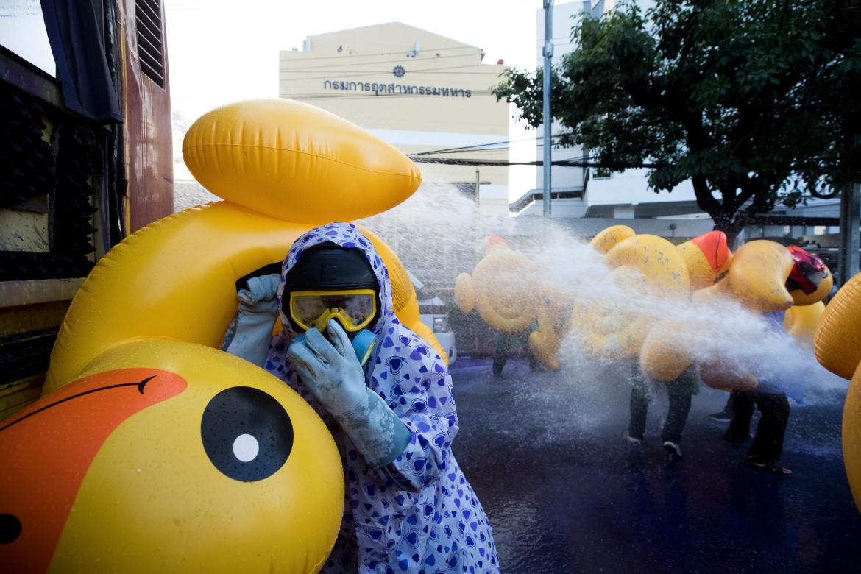 Pengunjuk rasa pro-demokrasi berlindung dengan bebek tiup saat polisi menyemprotkan meriam air.  [Foto Wason Wanichakorn / AP]