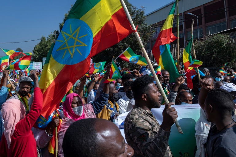 Ethiopians hold national flags at an event organised by city officials to honour the military in capital Addis Ababa [File: Mulugeta Ayene/AP]