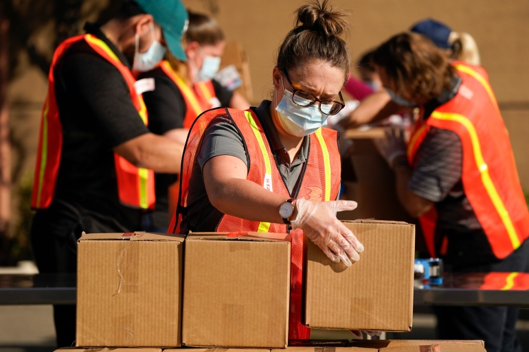 Volunteers pack boxes of food to be distributed to families in need for Thanksgiving Day at the Honda Center in Anaheim, California [Ashley Landis/AP]