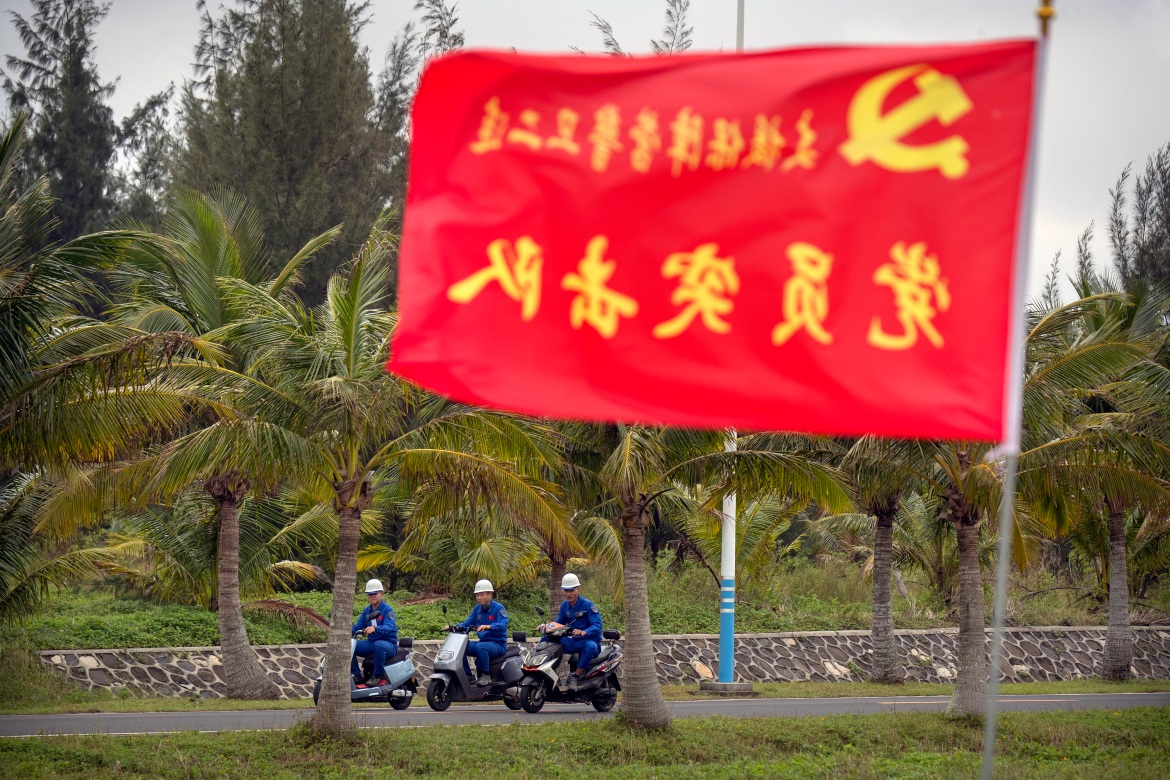Workers ride motorbikes near a flag with the logo of the Communist Party of China at the Wenchang Space Launch Site. [Mark Schiefelbein/AP Photo]