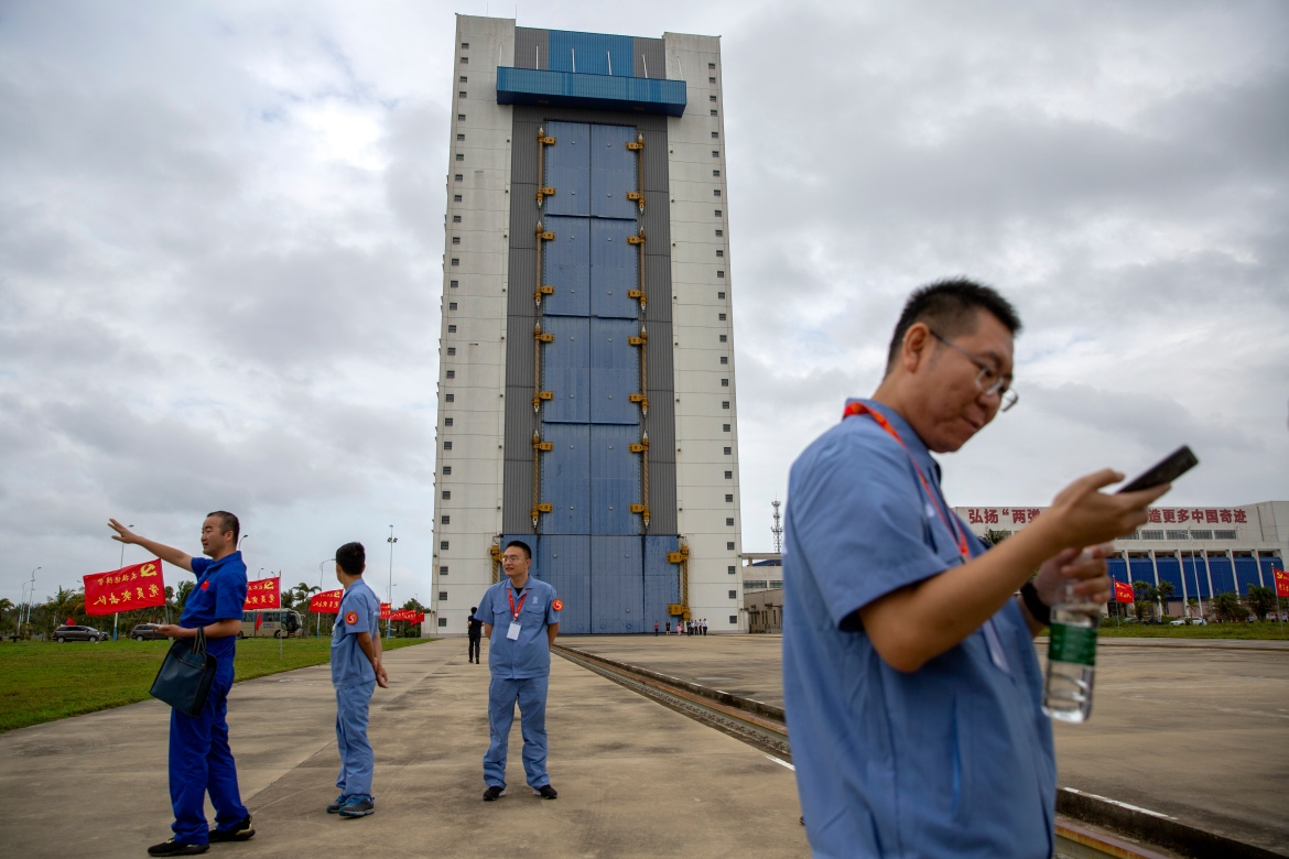 Workers gather near a building at the Wenchang Space Launch Site. [Mark Schiefelbein/AP Photo]