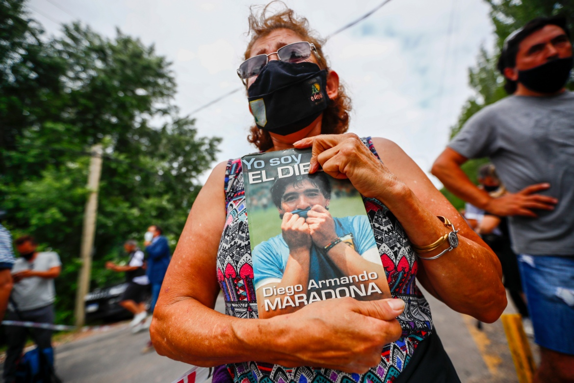 An Argentinian woman holds a copy of Maradona's biography. [Marcos Brindicci/AP Photo]