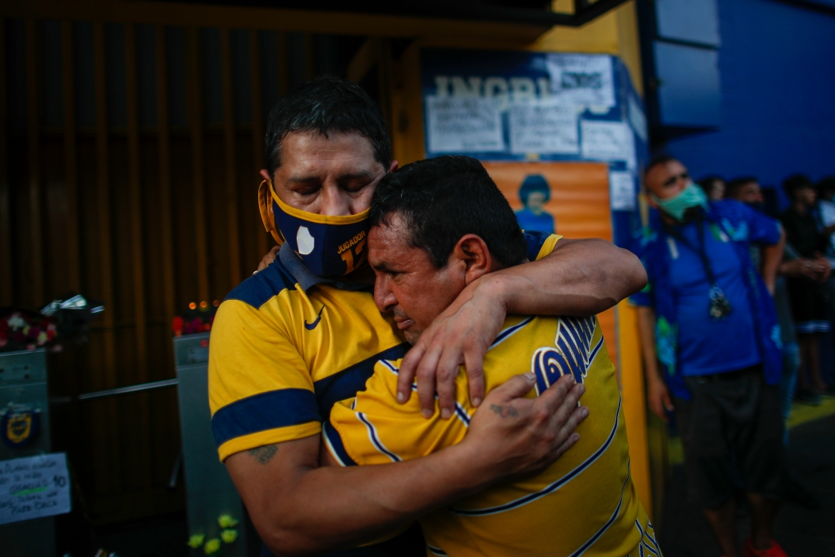 Fans mourn at the entrance of the Boca Juniors stadium, known as La Bombomera, in Buenos Aires. [Natacha Pisarenko/AP Photo]