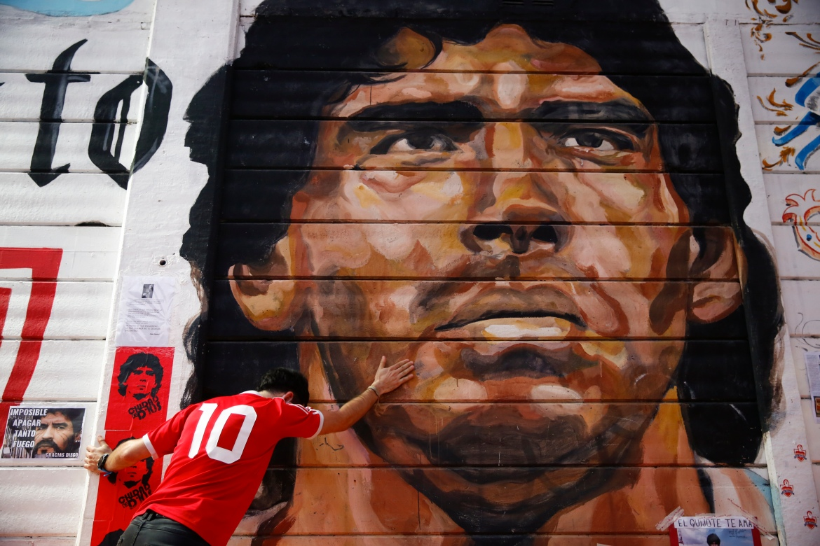 A boy touches a mural of Maradona outside the stadium of Argentinos Juniors football club. [Marcos Brindicci/AP Photo]