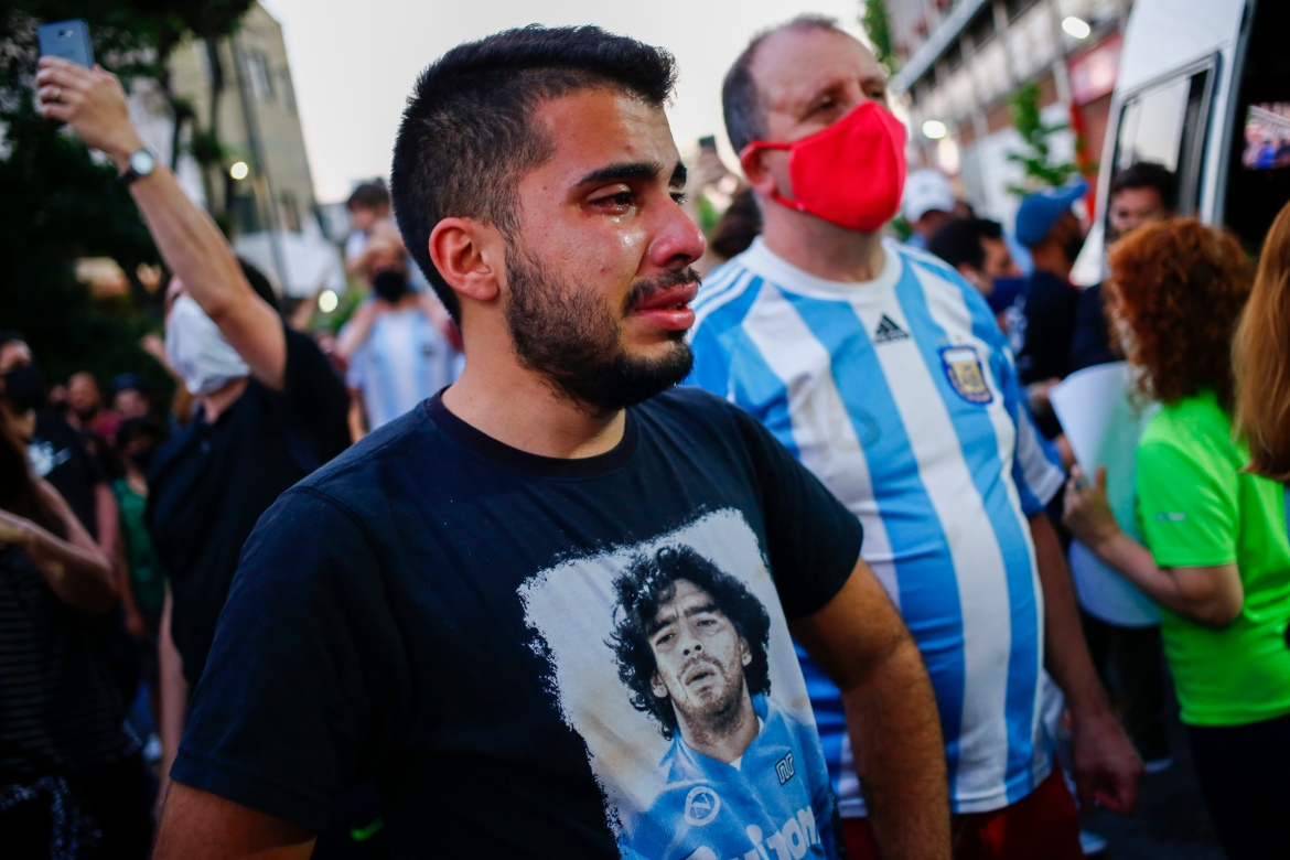 A man wearing a shirt with Maradona's face cries outside the stadium of the Argentinos Juniors football club, where he started as a professional footballer. [Marcos Brindicci/AP Photo]
