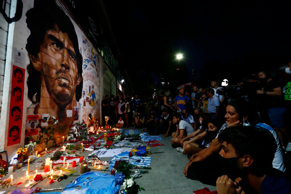 Football fans hold a vigil for Maradona outside the stadium of Argentinos Juniors football club. [Marcos Brindicci/AP Photo]