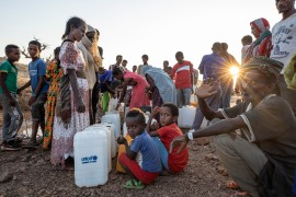 Refugees who fled the conflict in Ethiopia's Tigray region wait in line to pour water into containers at Um Raquba refugee camp in Qadarif, eastern Sudan [Nariman El-Mofty/AP]
