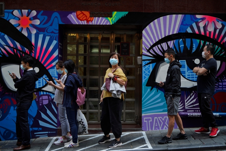People wearing face masks to help curb the spread of the coronavirus wait outside a bakery in Hong Kong, Monday, November 30, 2020 [Kin Cheung/ AP]
