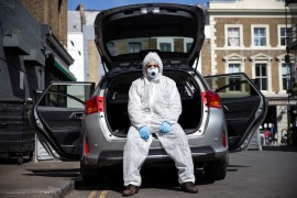 Uber driver Yasar Gorur wears personal protective equipment while cleaning his vehicle on April 14, 2020 in London, United Kingdom. Gorur says he wipes down the seats in his car every 2-3 trips and wears personal protective equipment whenever he drives [Hollie Adams/Getty Images]