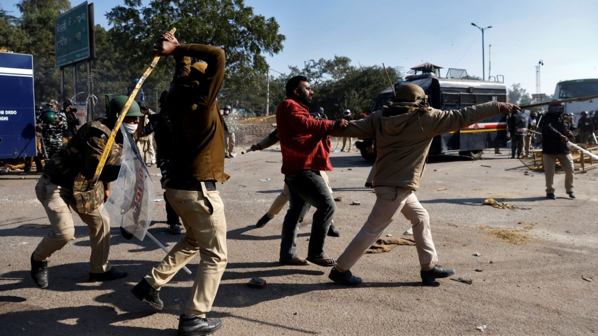 Policemen wield their batons against a farmer during a protest at Singhu border near New Delhi. [Danish Siddiqui/Reuters]