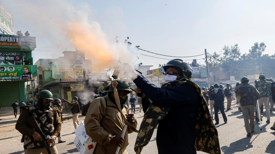A police officer fires tear gas to stop farmers from marching near New Delhi. [Danish Siddiqui/Reuters]
