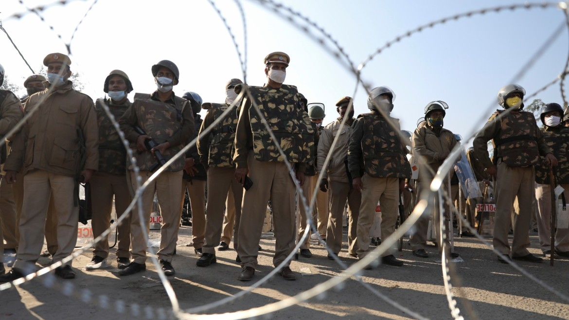 Police officers gather behind barbed wires to stop farmers from entering the national capital New Delhi at Singhu border on Friday. [Anushree Fadnavis/Reuters]