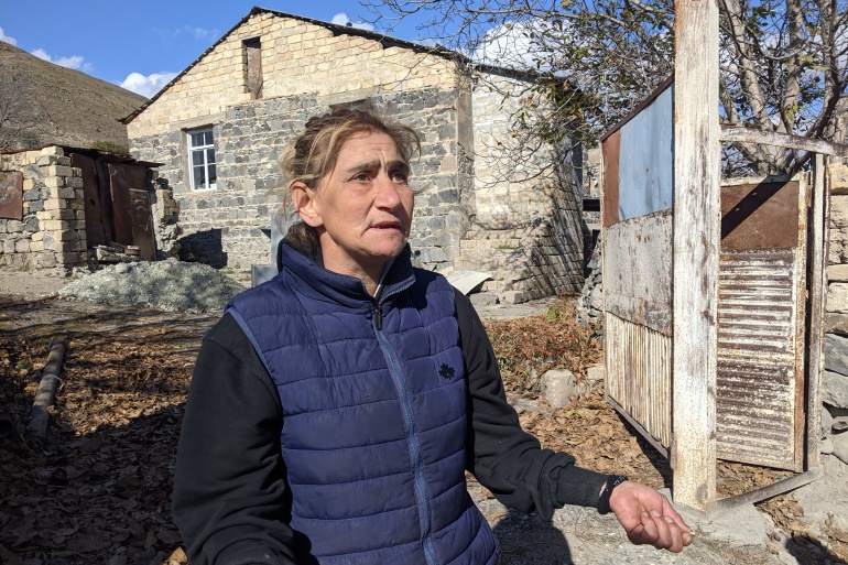 Karine Chakhelyan, outside her home in Kelbajar, says she feels she is being driven out 'like cattle' [Neil Hauer/Al Jazeera]