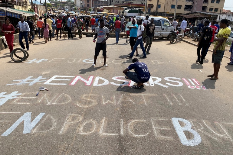 A demonstrator paints 'End Sars', referring to the Special Anti-Robbery Squad police unit, on a street during a protest demanding police reform in Lagos, Nigeria October 20, 2020. [Seun Sanni/Reuters]