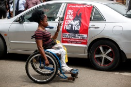 A woman takes a photograph with her mobile phone near a banner during a protest against the Special Anti-Robbery Squad (SARS), in the Ikeja district of Lagos, Nigeria on October 19 [File: Akintunde Akinleye/EPA]