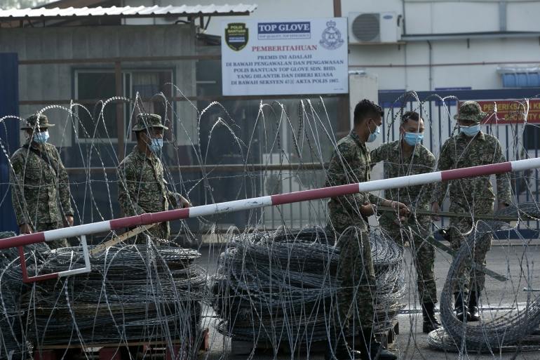 Top Glove worker hostels west of Kuala Lumpur have been under a strict lockdown for a week. Now the government has ordered phased factory closures so all staff can be tested for COVID-19 [Ahmad Yusni/EPA]