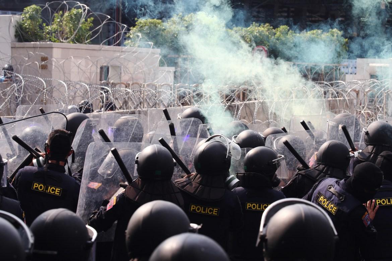 Petugas polisi berjaga-jaga setelah bom asap dilemparkan ke arah mereka oleh pengunjuk rasa pro-demokrasi.  [Narong Sangnak / EPA]