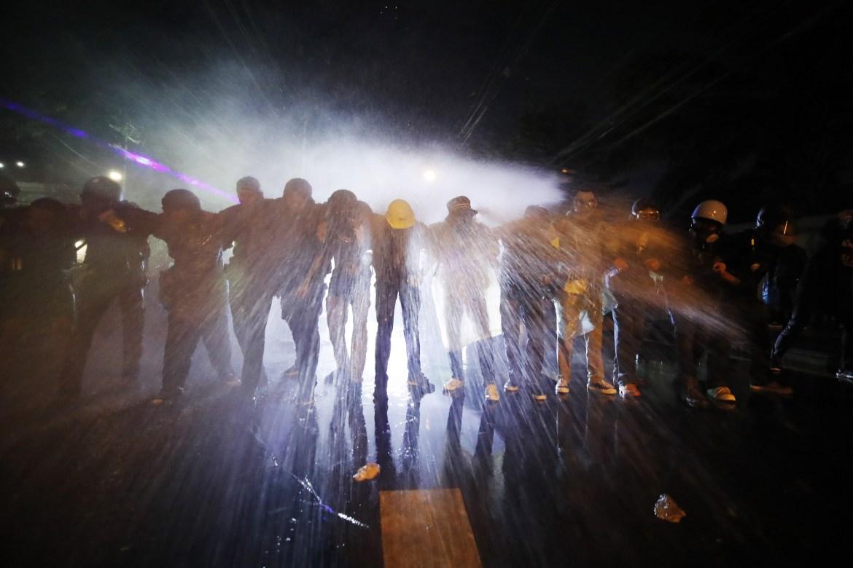 Pengunjuk rasa pro-demokrasi berdiri bersama saat dihantam meriam air yang ditembakkan oleh polisi.  [Diego Azubel / EPA]