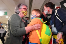 Families reunite as the first plane from Sydney arrives in Melbourne after the opening of state borders [James Ross/EPA]