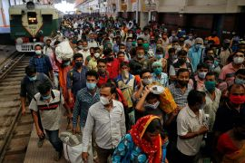 Passengers wearing face masks disembark from a suburban train after authorities resumed train services in Kolkata [File: Rupak De Chowdhuri/Reuters]
