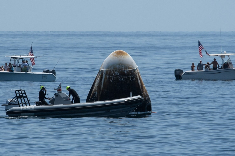 A recovery support team and recreational boaters surround the SpaceX's Crew Dragon capsule spacecraft off the coast of Pensacola, Florida on August 2 [File: Bloomberg]