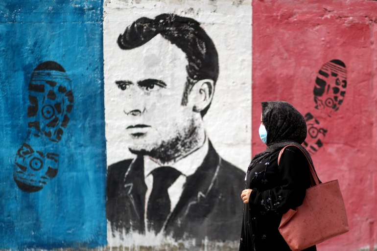 A Palestinian woman walks past an anti-French President Emmanuel Macron mural painted by an artist to protest against the publications of a cartoon of Prophet Mohammad in France and Macron's comments, in Gaza City, October 28, 2020. [Mohammed Salem/Reuters]