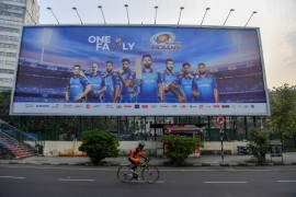 A cyclist in Mumbai rides past a hoarding showing Mumbai Indians cricketers, who won the tournament in UAE this year [File: Indranil Mukherjee/AFP]