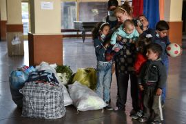 Zhanna Petrosyan (35), a refugee from the village of Tsapatagh of the Nagorno-Karabakh region and her seven children stand next to their belongings at a centre for refugees, in Yerevan, on October 24, 2020 after fleeing fierce fighting in the Nagorno-Karabakh region. File: AFP/Karen Minasyan]