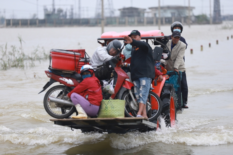 Residents hitch a ride on a forklift truck to dry land through flood waters brought by heavy rain from Typhoon Vamco in Thua Thien Hue province on November 15 [File: Huy Thanh/AFP]