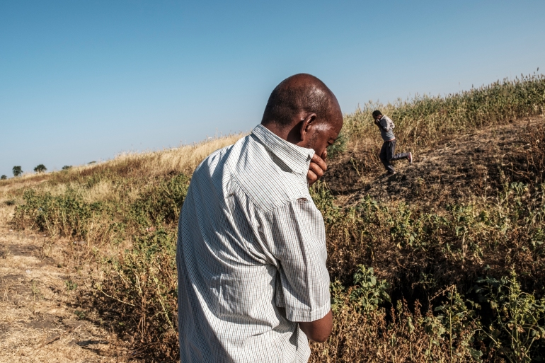Two men covering their noses near a ditch where more than 20 bodies lie, on the outskirts of Mai Kadra, November 21 [File: Eduardo Soteras/AFP]