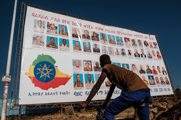 A youngster stands in front of a sign that depicts TPLF members as wanted by the Ethiopian federal police in Bahir Dar, Ethiopia, on November 26, 2020 [File: Eduardo Soteras/AFP]