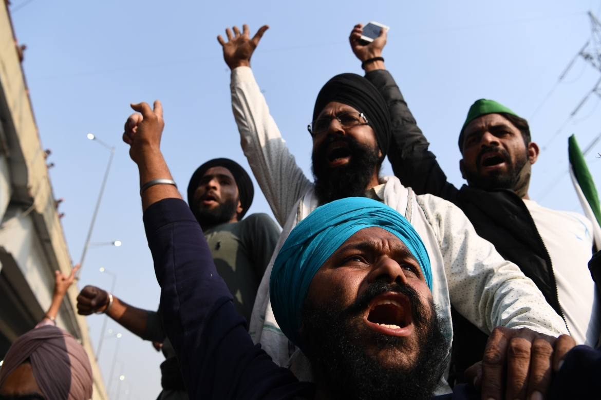 Farmers shout slogans at a police road block near the Delhi-Uttar Pradesh border in Ghazipurto to stop them from marching to New Delhi to protest against the central government's recent agricultural reforms [Sajjad Hussain/AFP]