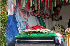 A handout picture provided by Iran's Defence Ministry on November 30, 2020, shows the coffin of slain top nuclear scientist Mohsen Fakhrizadeh in front of a large display depicting him next to Iran's Supreme Leader Ayatollah Ali Khamenei during the funeral ceremony in Tehran [File: Iranian Defence Ministry/AFP]