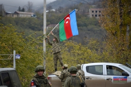 An Azerbaijani soldier fixes a national flag on a lamp post in the town of Lachin [Karen Minasyan/AFP]