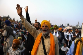 In this picture taken on December 5, 2020, Sandeep Singh, centre, 65, a farmer from Ludhiana in the northern Indian state of Punjab, shouts slogans during a rally along a road blocked by police to stop farmers from marching to New Delhi to protest against the central government's recent agricultural reforms [File: Money Sharma/AFP]