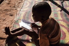 An Ethiopian refugee grade four pupil attends a class at a makeshift school in Um Rakuba refugee camp in Gadaref, eastern Sudan. [Yasuyoshi Chiba/AFP]