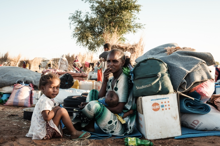 An Ethiopian refugee family who fled the conflict in Tigray sits next to their belongings at Um Rakuba refugee camp in Sudan [Yasuyoshi Chiba/AFP]
