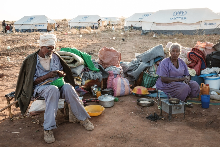 An Ethiopian refugee couple who fled the Tigray conflict sit with their belongings at Um Raquba refugee camp in Gadarif, eastern Sudan [Yasuyoshi Chiba/AFP]